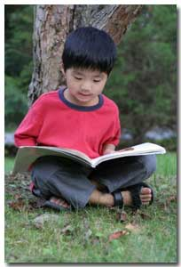 young boy reading a non-ficton text