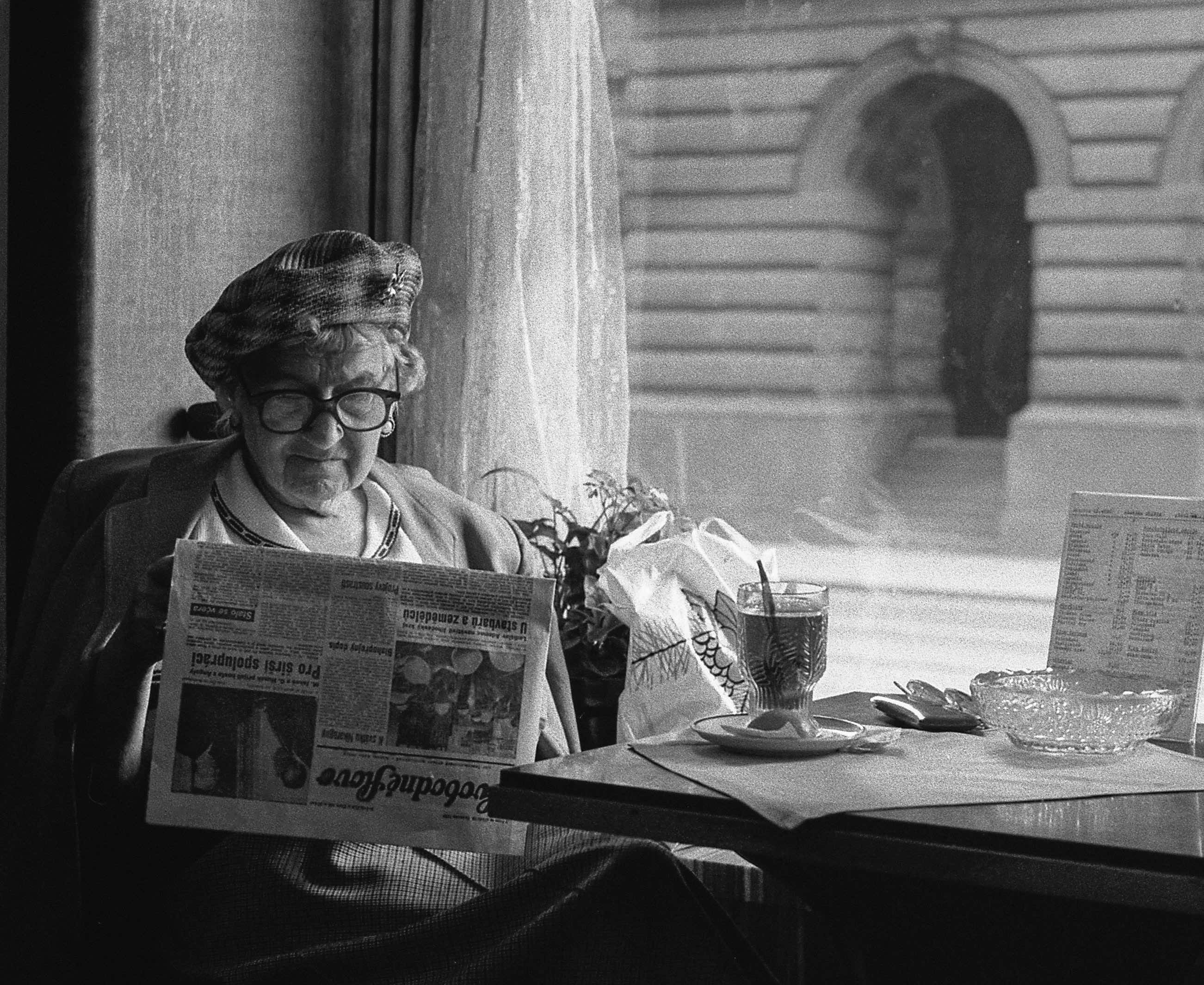 A woman reads a newspaper. You can learn to write reviews that sell.